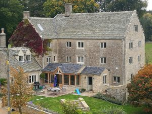 Cardinal immitation stone tile main roof and natural welsh slate lower roof