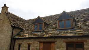 Cotswold natural stone tiles and vertical lead cladding on front of dormers
